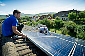 Two persons installing a solar plant, Freiburg im Breisgau, Black Forest, Baden-Wuerttemberg, Germany, Europe