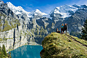 Hikers at lake Oeschinensee, Kandersteg, Bernese Oberland, Canton of Bern, Switzerland, Europe