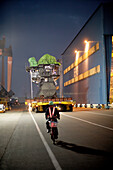 Moped driver leading a giant flatbed truck that is transporting MAN two-stroke engine from the test bed to the dry-dock, modular production at the laargest shipyard in the world, Hyundai Heavy Industries, HHI, in Ulsan, South Korea, Asia