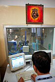 Engineer is monitoring a truck engine test stand underneath an image of Hindu deity Ganesha, MAN Force Trucks Private Limited, Pune, Maharashtra, India