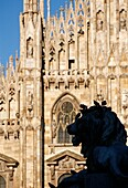 Milan  Italy  The Duomo  A monumental lion on the piazza silhouetted against the intricate facade of the Duomo