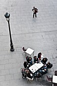 A street musician entertains cafe customers in the Plaza de Santa Cruz in the centre of Madrid