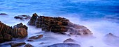 Night image of the Cantabrian Sea breaking on rocks area with long exposure time