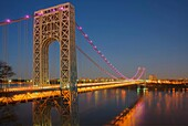 The George Washington Bridge, with pink lights in support of National Breast Cancer Awareness Month, spanning the Hudson River shortly after sunset in New York City, New York, USA.