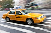 Motion blurred abstraction of taxi rushing through the streets of New York City, New York, USA