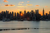 The rising sun shines through the buildings of the Manhattan skyline in New York City a few minutes after sunrise as viewed over the Hudson River looking east from New Jersey.