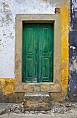 Green Wood Door with Hand Carved Stone against a Texured Wall in the Medieval Village Of Obidos