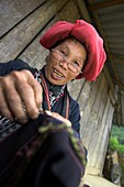 Red Zao hilltribe woman with spectacles sewing Ta Phin village near Sapa town north Vietnam