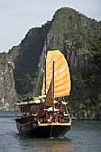 Motorized cruising junk with sails Halong Bay Vietnam
