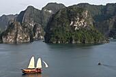 Cruising junk with sails hoisted Halong Bay Vietnam