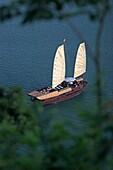 Eighty foot motorized cruising junk Lagoon Explorer from Titop Island lookout Halong Bay Vietnam