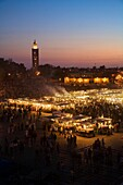 The La Koutoubia Mosque at Jemaa El Fna Square in Marrakech with food stalls and fruit sellers at nightime  Morocco