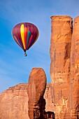 Hot air balloon drifts past the Thumb rock formation, Monument Valley, Navajo Tribal Park, Arizona USA