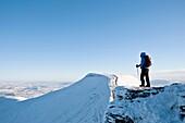 Female hiker viewing Pen Y Fan from Summit of Corn Du in winter, Brecon Beacons national park, Wales
