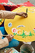 Painting parasols at the umbrella village Bo Sang, Chiang Mai province, Thailand
