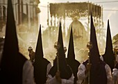 Penitents walk in front of a throne displaying a sculpture of Our Lady of Sorrows during an Easter Holy Week procession in Carmona village, Seville province, Andalusia, Spain, April 20, 2011
