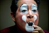 A clown puts on his make-up in front of a mirror in his hotel room before attending the 16th International Clown Convention: The Laughter Fair organized by the Latino Clown Brotherhood, in Mexico City, October 17, 2011