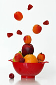 An Explosion Of Fruits (Nectarines, Apricots, Raspberries, Oranges And Lemons) In A Colander