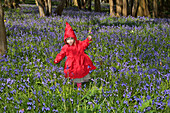 Young Girl Dressed As Little Red Riding Hood Walking In The Woods, France