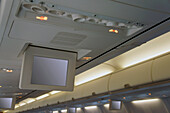 Drop down screens on an aircraft. Television and information monitors for passengers. Inflight entertainment.