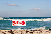 For Sale by Owner. Sign on beach. Sea shore, coastline, beach and sand. Selling up, property sale. Information sign.