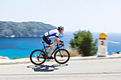 Bicycle rider at the Mediterranean coast, Andratx, Majorca, Balearic Islands, Spain