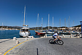 Bicycle rider passing marina, Port d'Andraitx, Andratx, Majorca, Balearic Islands, Spain
