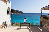 Bicycle rider resting on a bench at Mediterranean coast, Sant Elm, Majorca, Balearic Islands, Spain