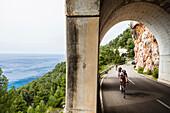 Bike racers in coast road tunnel at Mediterranean Sea, Estellencs, Mallorca, Spain