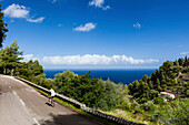 Bike racer on winding coast road, estate with terraced acreage, Banyalbufar, Mallorca, Spain