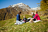 A family, two girls, a younger and an older woman sit on a meadow, autumn at Guarda, Engadin,  Grisons, Switzerland