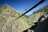 Woman walking on a suspension bridge over a canyon, Trift suspension bridge, Tieralplistock, Urner Alps, Bernese Oberland, Bern, Switzerland