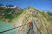 Hikers walking over a suspension bridge across a mountain lake, Trift glacier, Trift suspension bridge, Tieralplistock, Urner Alps, Bernese Oberland, Bern, Switzerland