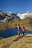 Woman and man hiking near mountain lake with view to Oberaarhorn and Finsteraarhorn, Bernese Alps, Bernese Oberland, UNESCO World Heritage Site Swiss Alps Jungfrau-Aletsch, Switzerland