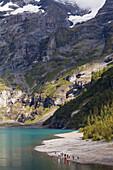 A group of teenagers at lake Oeschinen, Bernese Oberland, Canton of Bern, Switzerland