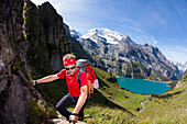 A man hiking, mountaineering above lake Oeschinen, Bernese Oberland, Canton of Bern, Switzerland