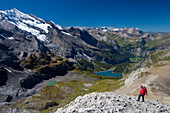 A man hiking, view to Doldenhorn, Oeschinensee, Kandersteg, Kandertal from ridge between Schwarzhorn and Bundstock, Bernese Oberland, Canton of Bern, Switzerland