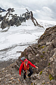 A male mountaineer, ascending along chains to the saddle of Gamchiluecke, view to Tschingelfirn glacier and Mount Mutthorn, Bernese Oberland, Canton of Bern, Switzerland