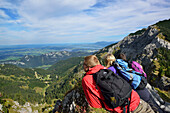 Young woman and two young men enjoying the view from Aggenstein to Fuessen, Aggenstein, Tannheim range, Tyrol, Austria