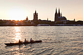 Rowboat on the Rhine river in front of the old town with Great St Martin church and cathedral, Cologne, North Rhine-Westphalia, Germany, Europe