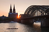 Rowboat on the Rhine river in front of cathedral and Hohenzollern bridge at sunset, Cologne, North Rhine-Westphalia, Germany, Europe