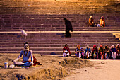 Holy man prays at Dasaswamedh Ghat alongside Ganges river at dawn, Varanasi, Uttar Pradesh, India