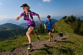 Trailrunning, Trail running, Trail, Ramsau, Dachstein, Styria, Austria, couple, woman, man, meadow, running, walking, run, mountains, mountain run, dog jogging, sport, fitness, health,. Trailrunning, Trail running, Trail, Ramsau, Dachstein, Styria, Austri