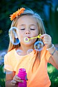 alone, blow, blowing, bubble, child, color image, contrast, female, flower, fun, girl, hair, holding, human, innocence, kid, looking at camera, nature, one, open, Orange, outdoors, people, shade, shirt, single, solo, vertical, vibrant, Vibrant colors, was