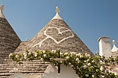 Conical dry stone roof of trulli house, with painted heart symbol, Alberobello, Bari province, Puglia region, Italy