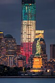 Two symbols of freedom, the Statue of Liberty and the Freedom Tower One World Trade Center, are illuminated at twilight in New York City. The Freedom Tower, lighted in the red, white, and blue colors of the American flag, is scheduled for completion in 20