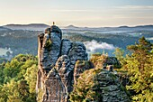 View to the rock Moench also Moenchstein monk or monkstone The Moench is a popular climbing tower rock in the National Park Saxon Switzerland near the health resort Rathen in the Elbe Sandstone Mountains At the top is a weather vane in the form of a monk,