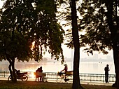 A young couple embraces on a park bench overlooking Hanoi´s West Lake, one of the few natural escapes within the bustling city  Their parked motorbike and a fisherman are nearby   Vietnam is underging a major economic transformation, throwing the youth of
