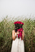Young Woman Holding Bouquet of Red Roses in Front of Face in Grassy Field