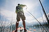 Man Flyfishing on Paddle Board on Lake